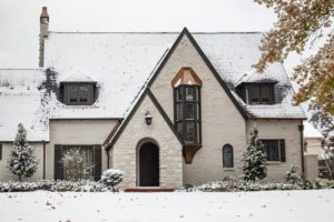 a painter brick home with snow on the roof and lawn