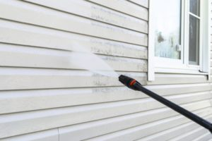 a person pressure washing the outside of their house